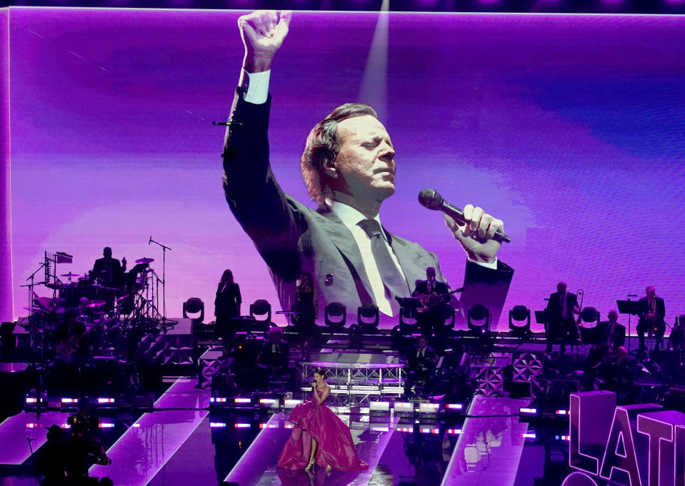 Julio Iglesias is seen on screen as Natalia Jimenez performs during a living legends tribute at the 21st Latin Grammy Awards, airing on Thursday, Nov. 19, 2020, at American Airlines Arena in Miami. (AP Photo/Marta Lavandier)