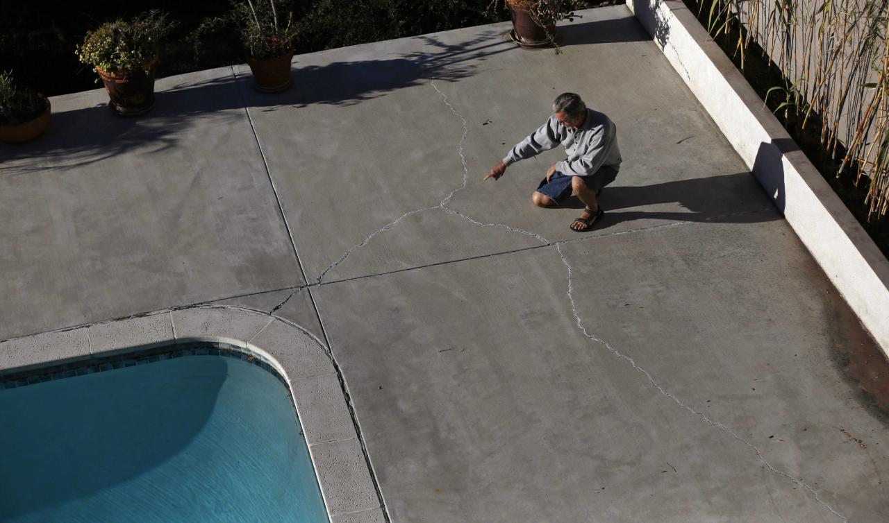 "Homeowner Gary Gless points at cracks in cement in his backyard in Los Angeles, California December 11, 2013. The United States has a long history of keeping industrial activity out of middle and upper-middle-class residential neighborhoods. But that is starting to change with the spread of new technology for oil and gas drilling, such as horizontal drilling and hydraulic fracturing, or ""fracking."" Freeport-McMoRan, part of Freeport-McMoRan Copper & Gold Inc, said that, for the past three years, its surveys of the oilfield and surrounding communities have found no connection between its activities and ""localized claims of property damage."" It said it would continue to evaluate the issue. Picture taken December 11, 2013. To match Analysis FRACKING-HOMEOWNERS/ REUTERS/Mario Anzuoni (UNITED STATES - Tags: REAL ESTATE BUSINESS ENERGY)"
