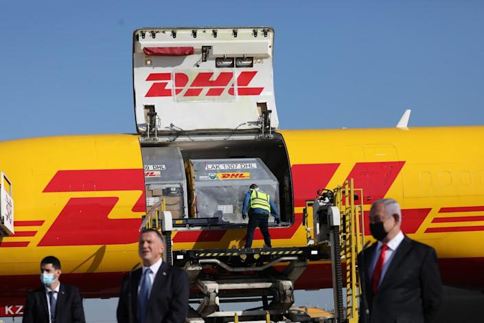Benjamin Netanyahu stands with other men in front of a cargo jetliner with the DHL logo.