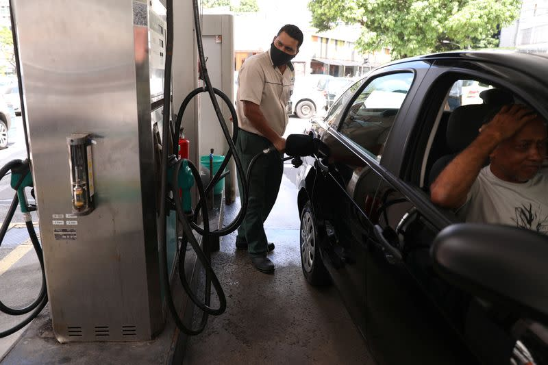 A worker pumps a car with gasoline at a gas station in Rio de Janeiro