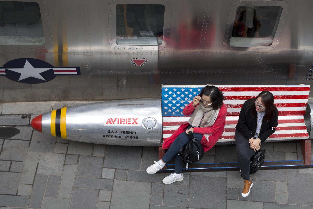 Chinese women sit on a bench with a U.S. flag theme outside an apparel store in Beijing Friday, March 23, 2018. China announced on Friday a $3 billion list of U.S. goods including pork, apples and steel pipe on Friday it said may be hit with higher tariffs in a spiraling trade dispute with President Donald Trump that companies and investors worry could depress global commerce. (AP Photo/Ng Han Guan)