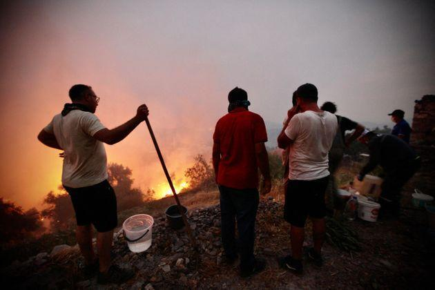 Fire crews, helped by inhabitants, work to put out a fire spreading in the Aegean coast city of Oren, near Milas, in the holiday region of Mugla on August 3, 2021 (Photo: STR via Getty Images)