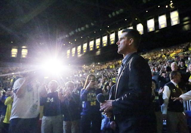 Michigan football coach Jim Harbaugh walks onto the basketball court where he addressed fans during halftime of an NCAA college basketball game between Michigan and Illinois in Ann Arbor, Mich., Tuesday, Dec. 30, 2014. (AP Photo/Carlos Osorio)