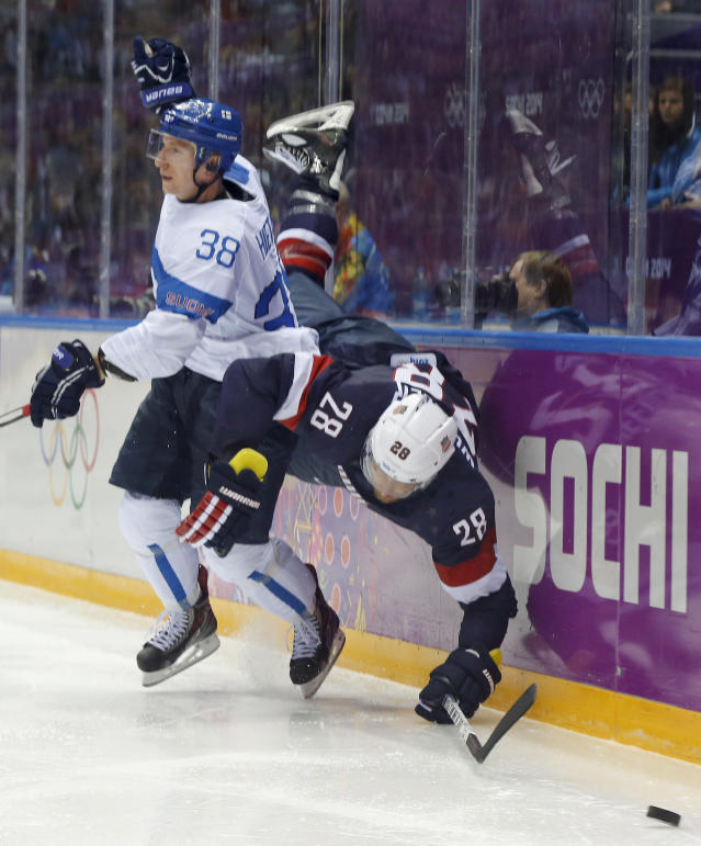 Finland defenseman Juuso Hietanen and USA forward Blake Wheeler crash the boards during the third period of the men's bronze medal ice hockey game at the 2014 Winter Olympics, Saturday, Feb. 22, 2014, in Sochi, Russia. (AP Photo/Mark Humphrey)