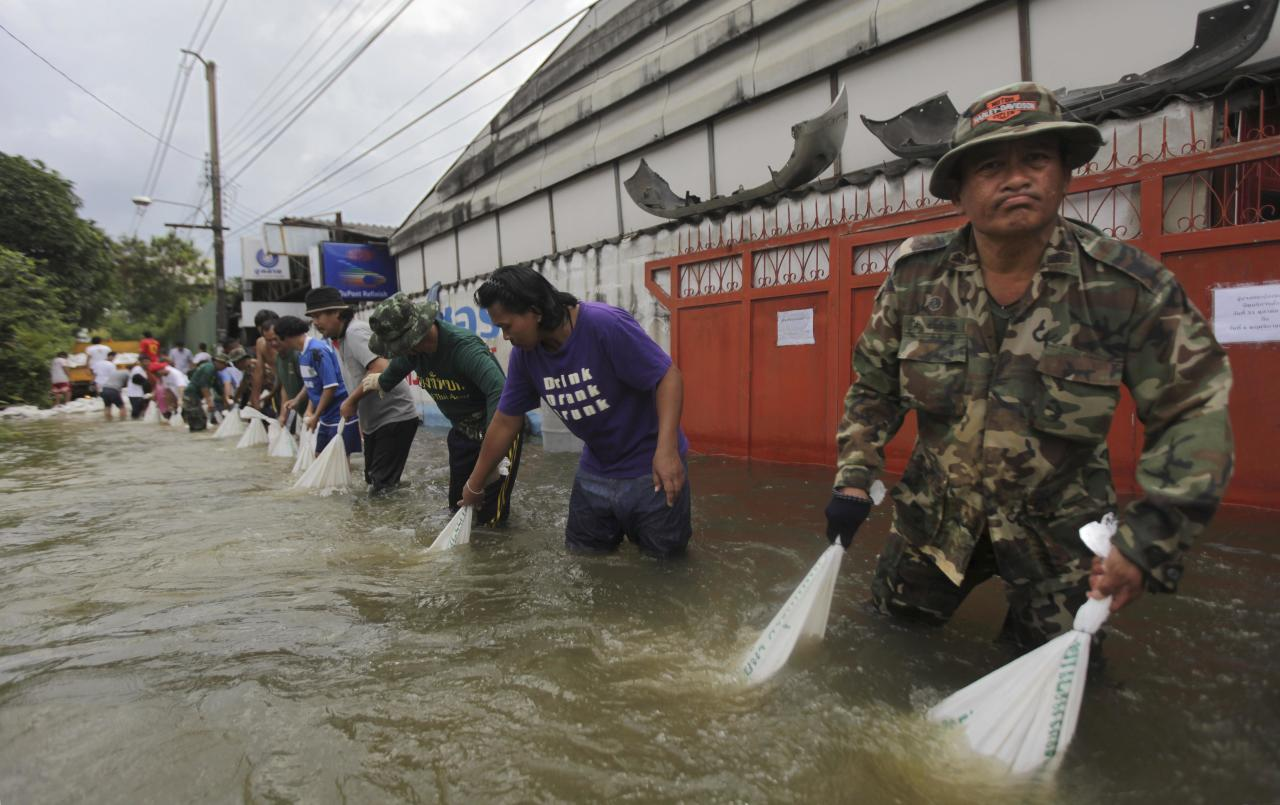 Thai soldiers and residents carry sandbags to fortify a wall breached by swollen Chao Phraya river in Bangkok, Thailand, Saturday, Oct. 29, 2011. The complex network of flood defenses erected to shield Thailand's capital from the country's worst floods in nearly 60 years was put to the test Saturday as coastal high tides hit their peak. (AP Photo/Altaf Qadri)