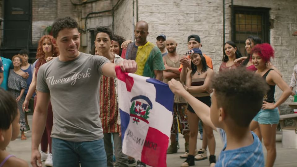 Usnavi and a young boy hold the Dominican Republic flag together.