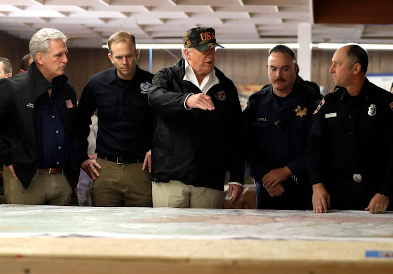 President Donald Trump looks at a map as he visits with first responders and local officials at an operations center responding to the wildfires, Saturday, Nov. 17, 2018, in Chico, Calif. At left is House Majority Leader Kevin McCarthy of Calif., and FEMA Administrator Brock Long.