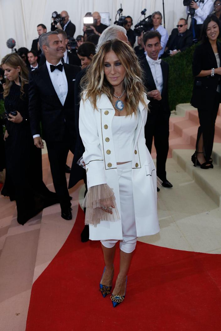 Sarah Jessica Parker wears white pants, a white shirt, and a white jacket on a red carpet.