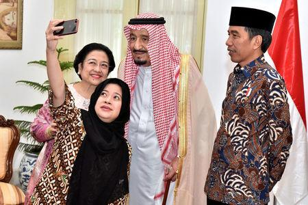 Indonesian President Joko Widodo watches as former president Megawati Sukarnoputri and her daughter Puan Maharani, a minister in his cabinet, take a selfie with Saudi Arabia's King Salman at the presidential palace in Jakarta