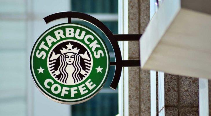 the Starbucks (SBUX) logo on a sign outside of a coffee shop
