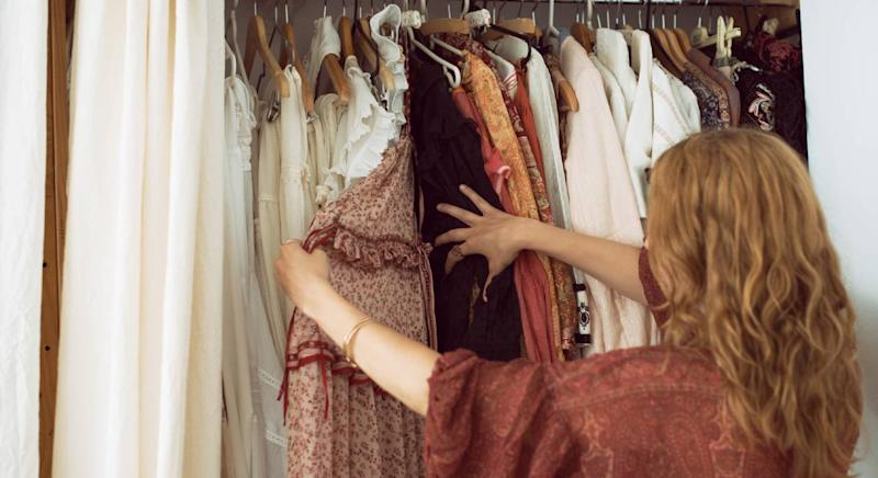 A woman looks through her wardrobe [Photo: Getty]