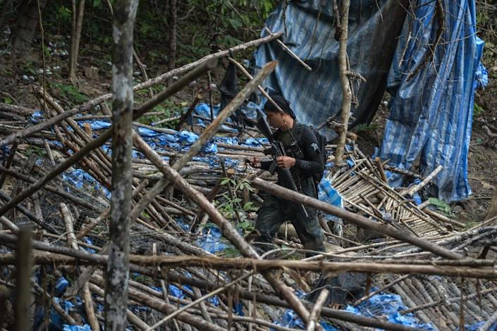 A Malaysian police officer inspects an abandoned migrant camp used by people-smugglers in a jungle at Bukit Wang Burma in Malaysia's Perlis state, bordering Thailand, on May 26, 2015 (AFP Photo/Mohd Rasfan)