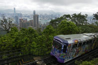 A Peak Tram passes an uphill of the Victoria Peak with a backdrop of Hong Kong on June 17, 2021. Hong Kong's Peak Tram is a fixture in the memories of many residents and tourists, ferrying passengers up Victoria Peak for a bird's eye view of the city's many skyscrapers. (AP Photo/Vincent Yu)