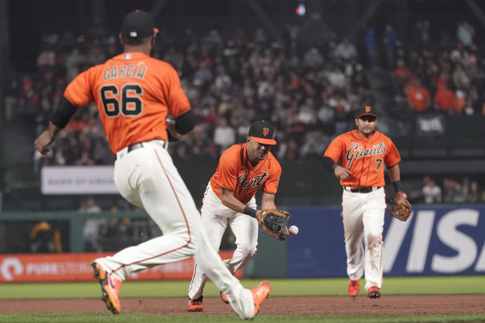 San Francisco Giants first baseman LaMonte Wade Jr., middle, commits a fielding error between pitcher Jarlin Garcia (66) and second baseman Donovan Solano on a ground ball hit by Pittsburgh Pirates' Ben Gamel during the seventh inning of a baseball game in San Francisco, Friday, July 23, 2021. (AP Photo/Jeff Chiu)