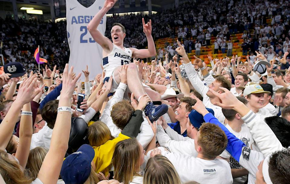 Fans celebrate with Utah State forward Justin Bean on the court after Utah State defeated Nevada 81-76 in an NCAA college basketball game Saturday, March 2, 2019, in Logan, Utah. (Eli Lucero/The Herald Journal via AP)