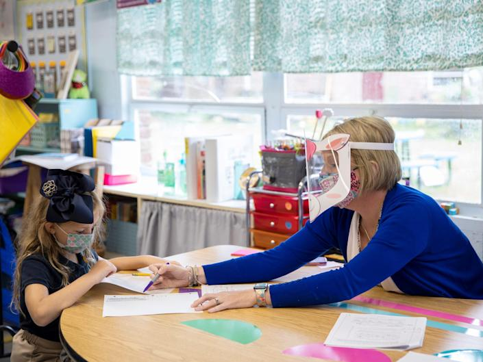 A teacher and a child wearing masks in a Mississippi classroom.