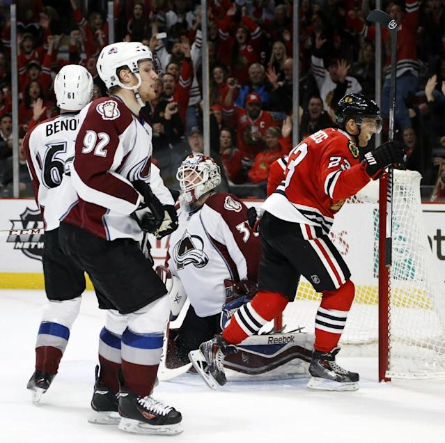 Chicago Blackhawks right wing Kris Versteeg (23) celebrates his goal past Colorado Avalanche goalie Jean-Sebastien Giguere (35) Andre Benoit (61) and Gabriel Landeskog (92) during the second period of an NHL hockey game Friday, Dec. 27, 2013, in Chicago. (AP Photo/Charles Rex Arbogast)