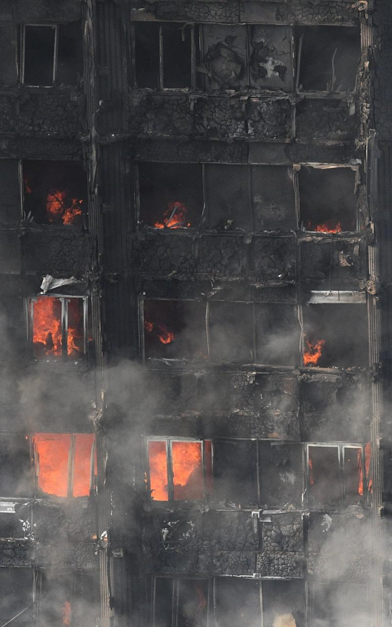 Remaining fire burns at the Grenfell Tower apartment block in North Kensington - Credit: EPA