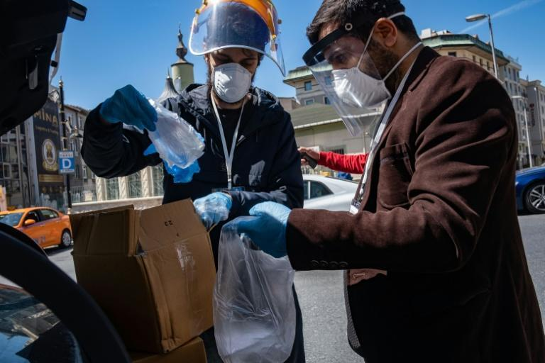 Members of the Tarlabasi Solidarity Network prepare aid packages of disinfectants, gloves, face masks as well as food cards for African migrants in Istanbul