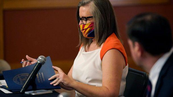 PHOTO: Arizona Secretary of State Katie Hobbs, left, signs documents to certify the election results for federal, statewide, and legislative offices and statewide ballot measures at the official canvass in the Arizona Capitol, Nov. 30, 2020, in Phoenix. (Ross D. Franklin/Pool via AP, FILE)