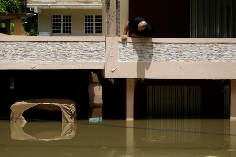 A man looks at damages on his flooded house, close to the dam of the Guajataca lake after the area was hit by Hurricane Maria in Guajataca, Puerto Rico September 23, 2017. REUTERS/Carlos Garcia Rawlins