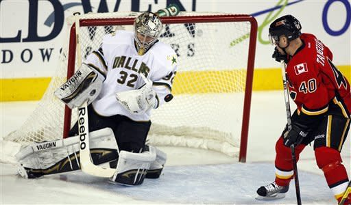 Dallas Stars goalie Kari Lehtonen, from Finland, loses the puck as Calgary Flames' Alex Tanguay looks for a rebound during second period NHL hockey action in Calgary, Alberta, Monday, March 26, 2012. (AP Photo/The Canadian Press, Jeff McIntosh)