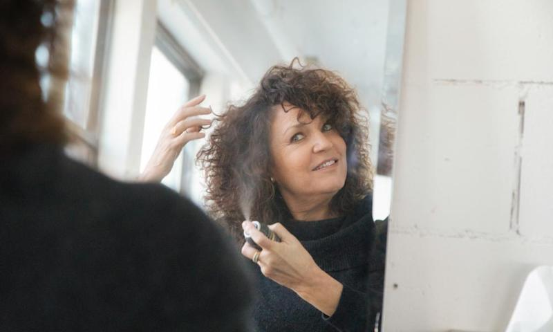 Woman applying dry shampoo to her hair at home.