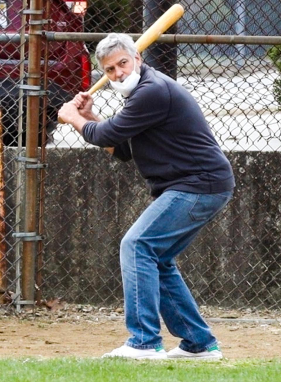 <p>George Clooney takes a few swings in between filming his upcoming film <em>The Tender Bar</em> on Wednesday in Boston.</p>