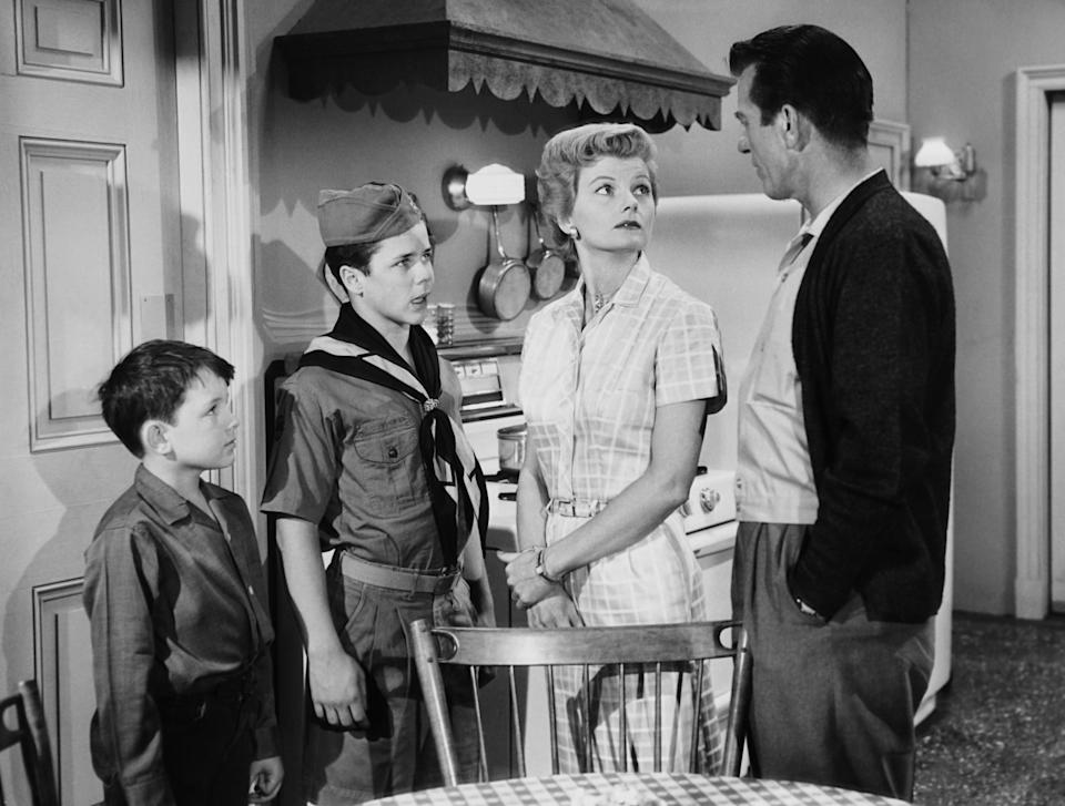 Jerry Mathers, Tony Dow, Barbara Billingsley, and Hugh Beaumont stand in the kitchen