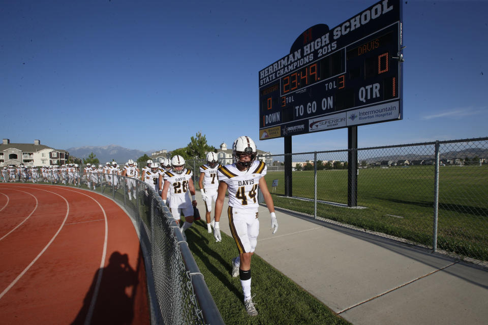 Davis players walk off the field before the start of their high school football game against Herriman on Thursday, Aug. 13, 2020, in Herriman, Utah. Utah is among the states going forward with high school football this fall despite concerns about the ongoing COVID-19 pandemic that led other states and many college football conferences to postpone games in hopes of instead playing in the spring. (AP Photo/Rick Bowmer)