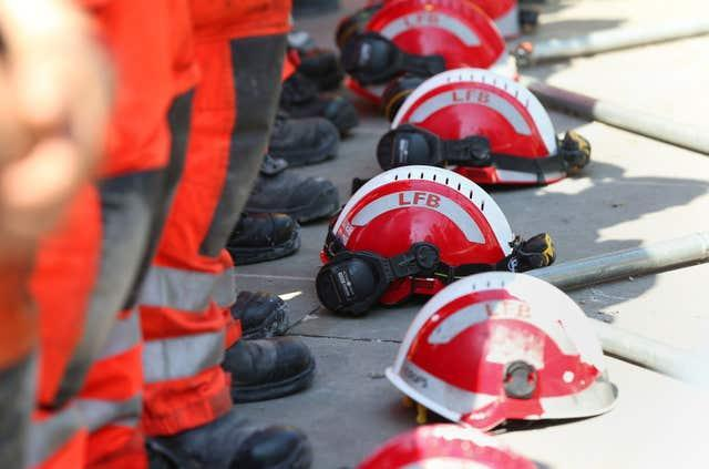 Firefighters lay their helmets on the ground during a minute's silence near to Grenfell Tower (Jonathan Brady/PA)