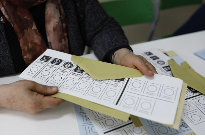 An official female holds a ballot voting paper at a polling station during the municipal elections in Ankara, Turkey, Sunday, March 31, 2019. Turkish citizens have begun casting votes in municipal elections for mayors, local assembly representatives and neighborhood or village administrators that are seen as a barometer of Erdogan's popularity amid a sharp economic downturn. (AP Photo/Burhan Ozbilici)