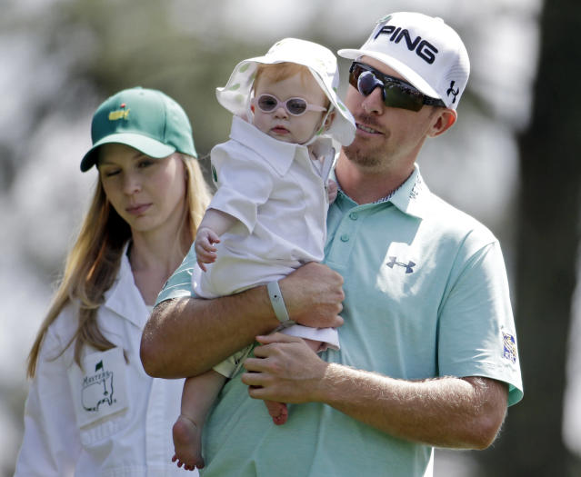 Hunter Mahan carries his daughter Zoe as he walks down the first fairway with his wife Kandi during the par three competition at the Masters golf tournament Wednesday, April 9, 2014, in Augusta, Ga. (AP Photo/Darron Cummings)