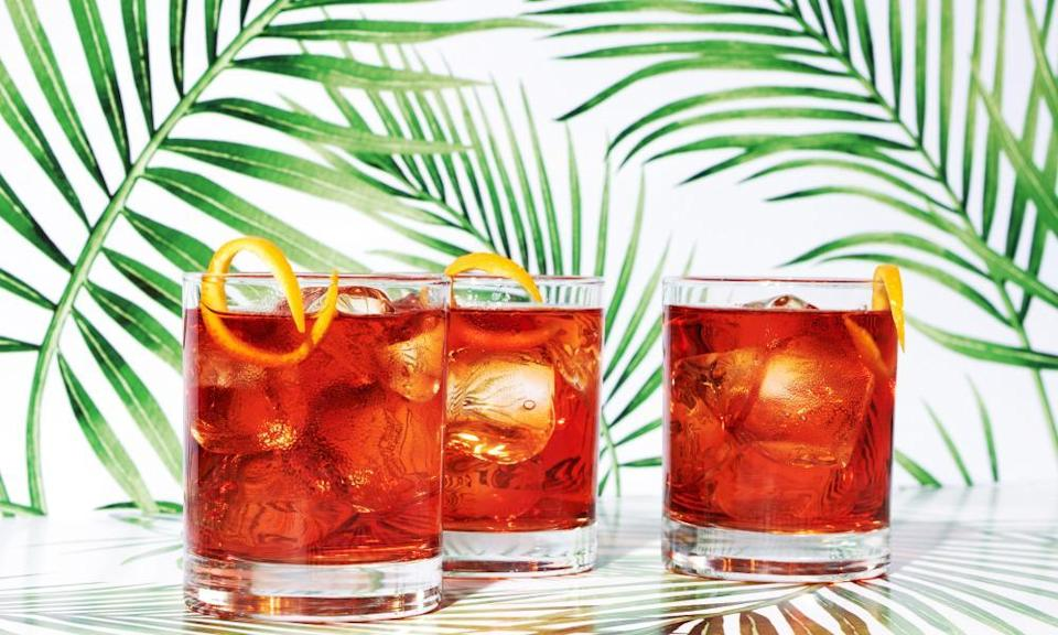 Three red negroni cocktails on tropical background