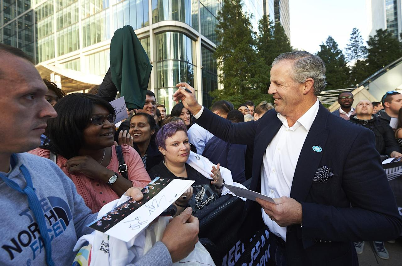 Former New Zealand rugby captain Sean Fitzpatrick (R) signs autographs for fans during a 2015 Rugby World Cup New Zealand team event in Canary Wharf in east London on September 25, 2015. New Zealand face Georgia in their next 2015 Rugby World Cup fixture on October 2. AFP PHOTO / NIKLAS HALLE'N (AFP Photo/NIKLAS HALLE'N)
