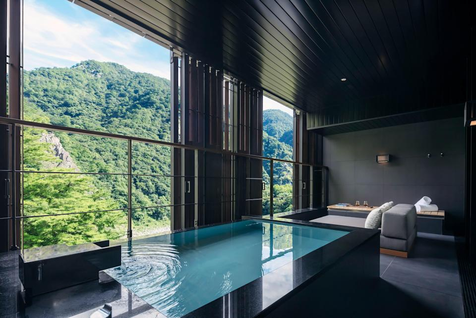 """<p><strong>Why did this hotel catch your attention? What's the vibe?</strong><br> The drive in takes you up a long, winding mountain road, past several hot springs resorts. But when you pull up to the Hoshinoya, it's clear the hotel is unlike any other, with its landscaped entrance; sleek, black walls; and immediate calming effect. Like a traditional Japanese hotel, the staff greets you outside the door with hot towels and beverages, and the entire check-in process is seamless.</p> <p><strong>What's the backstory?</strong><br> The Hoshinoya Guguan is the Japanese chain's first opening in <a href=""""https://www.cntraveler.com/story/a-road-trip-through-taiwans-hot-springs-and-tea-plantations?mbid=synd_yahoo_rss"""" rel=""""nofollow noopener"""" target=""""_blank"""" data-ylk=""""slk:Taiwan"""" class=""""link rapid-noclick-resp"""">Taiwan</a>. With several properties in Japan, as well as hotels in Bali and Oahu, Hoshinoya has recently begun spreading its wings beyond its home country. <a href=""""https://www.cntraveler.com/hotels/tokyo/hoshinoya-tokyo?mbid=synd_yahoo_rss"""" rel=""""nofollow noopener"""" target=""""_blank"""" data-ylk=""""slk:Hoshinoya's"""" class=""""link rapid-noclick-resp"""">Hoshinoya's</a> CEO was originally skeptical about bringing his <em>onsen</em> resorts to Taiwan—but then visited the Guguan region and discovered the onsen waters were as impressive as the ones found in Japan.</p> <p><strong>Tell us all about the accommodations. Any tips on what to book?</strong><br> There are 50 rooms total at the hotel. The bedrooms are minimally decorated with low beds, and the living room area features plenty of seating space—either two tables and a chair or an area with low-slung sofas around a coffee table—and large daybeds that face out to the valley view. Depending on what floor you're on, stairs lead up or down to each room's onsen area, which provides additional privacy if you're sharing a room with family or friends. Two smart design touches we loved: lighting panels with a variety of mood settings, and the"""