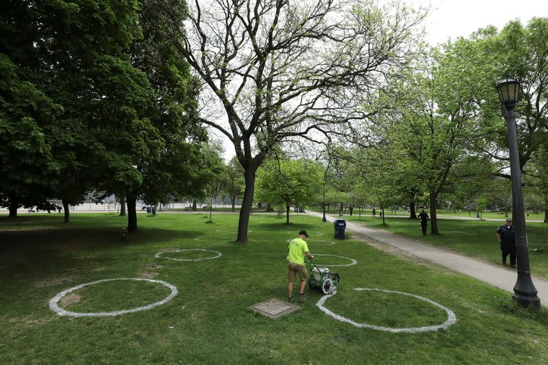Park staff paint circles to help visitors maintain social distancing to slow the spread of the coronavirus disease in Toronto