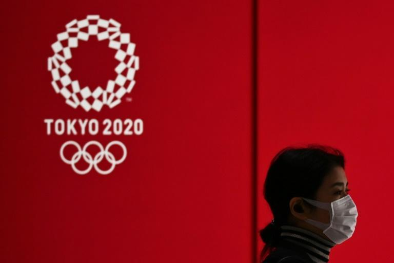 A woman wearing a face mask walks past a display showing the 2020 Olympics logo in Tokyo as support among the Japanese public for staging the Games wanes badly