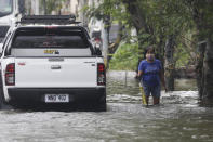 A resident negotiates a flooded road due to Typhoon Molave in Pampanga province, northern Philippines on Monday, Oct. 26, 2020. A fast moving typhoon has forced thousands of villagers to flee to safety in provinces. (AP Photo/Aaron Favila)