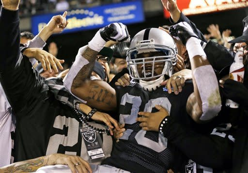 Oakland Raiders running back Darren McFadden is mobbed by fans after scoring a touchdown on a 6-yard pass during the second quarter of an NFL football game against the Denver Broncos in Oakland, Calif., Thursday, Dec. 6, 2012. (AP Photo/Marcio Jose Sanchez)