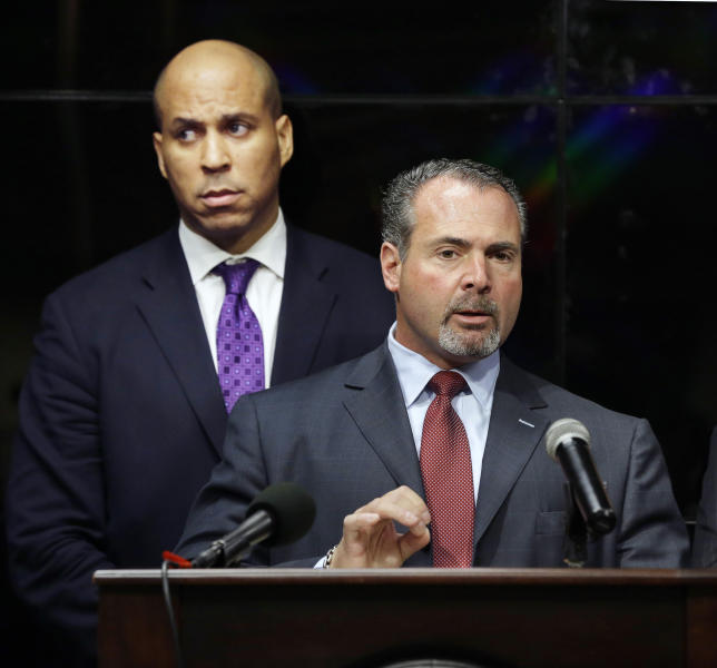 Newark Mayor Cory Booker, left, listens as Police Director Samuel DeMaio, answers a question about arrest of three men after a video surfaced that showed a naked young man being whipped because of his father's debt, during a news conference on Wednesday, Feb. 13, 2013. The men identified are 22-year-old Ahmad Holt, 31-year-old Raheem Clark and 23-year-old Jamaar Gray. Police say Holt administered the beating, using a belt provided by Clark. Charges include robbery and aggravated assault. The video shows a 21-year-old man being forced to strip and then whipped with a belt, supposedly because his father owed someone $20. Subsequent to the police investigation, Nicole A. Smith was arrested for drug possession. (AP Photo/Mel Evans)