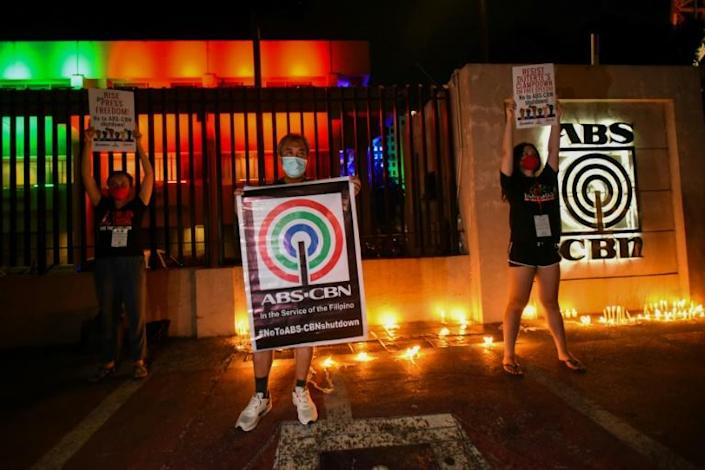 Outside ABS-CBN's broadcast compound, a handful of supporters waved placards against a backdrop of burning candles (AFP Photo/Maria TAN)