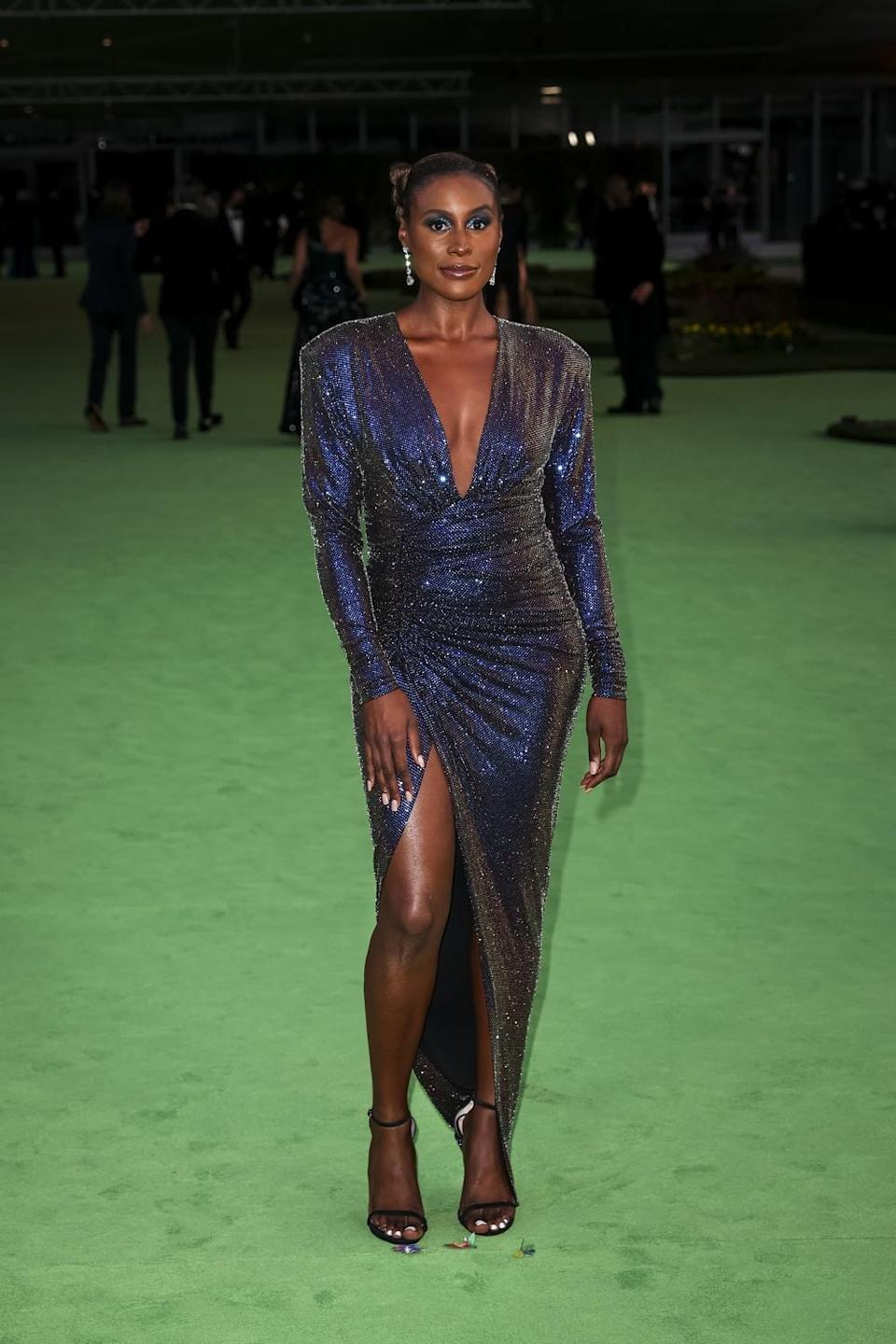 A woman in a sparkly blue dress posing on a green carpet