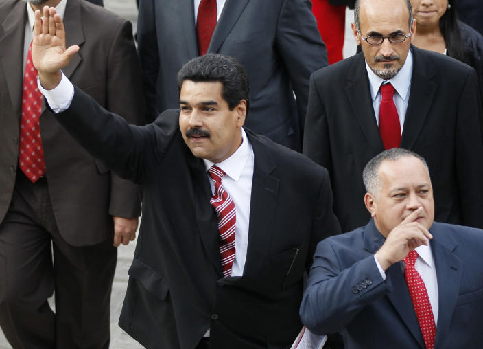 """Venezuela's Vice President Nicolas Maduro, left, and Diosdado Cabello, president of Venezuela's National Assembly, gesture to supporters as they arrive to the National Assembly for the state-of-the-nation address in Caracas, Venezuela, Thursday, Feb. 28, 2013. Maduro, Chavez's self-appointed successor, said on television that his boss """"is battling there for his health, for his life, and we're accompanying him."""" (AP Photo/Ariana Cubillos)"""