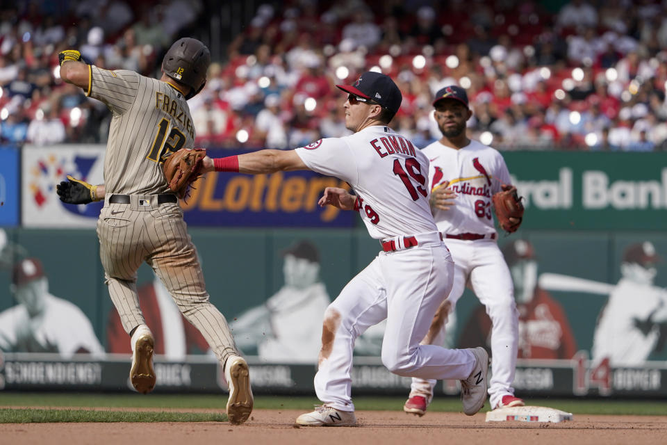 St. Louis Cardinals second baseman Tommy Edman tags out San Diego Padres' Adam Frazier, left, while shortstop Edmundo Sosa, right, watches as Edman turns the double play during the seventh inning of a baseball game Sunday, Sept. 19, 2021, in St. Louis. The Padres' Jurickson Profar was out at first. (AP Photo/Jeff Roberson)