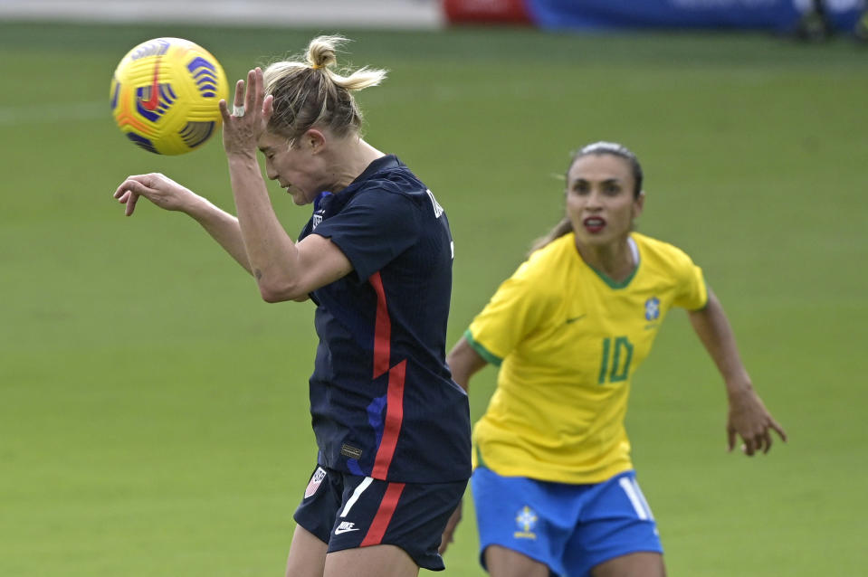 United States defender Abby Dahlkemper (7) heads a ball in front of Brazil midfielder Marta (10) during the first half of a SheBelieves Cup women's soccer match, Sunday, Feb. 21, 2021, in Orlando, Fla. (AP Photo/Phelan M. Ebenhack)