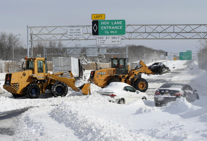 Payloaders clear snow from the Long Island Expressway just west of exit 59 Ocean Ave where several cars and a truck are abandoned after a snow storm on Saturday, Feb. 9, 31, 2013, in Ronkonkoma , N.Y. (AP Photo/Kathy Kmonicek)