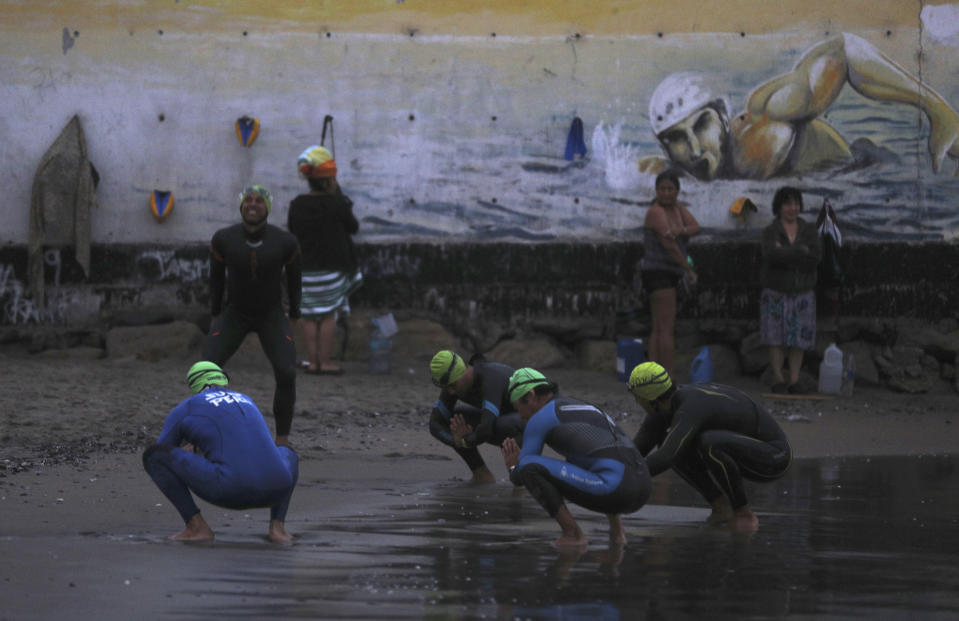 Open sea swimmers warm-up on Pescadores beach in Lima, Peru, at sunrise Tuesday, April 27, 2021. One of the few sporting disciplines that have been maintained during the coronavirus pandemic is swimming, which due to the closure of the swimming pools, has moved to the open sea. (AP Photo/Martin Mejia)