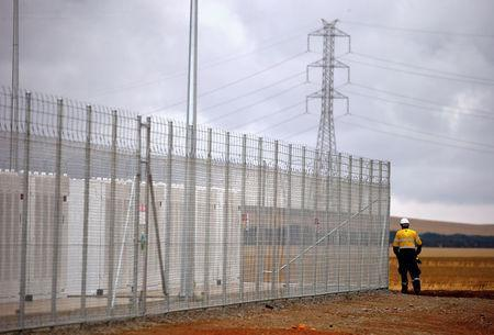 A worker walks along the fence for the compound housing the Hornsdale Power Reserve, featuring the world's largest lithium ion battery made by Tesla, during the official launch near the South Australian town of Jamestown, in Australia, December 1, 2017. REUTERS/David Gray