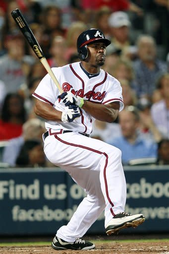 Atlanta Braves' Michael Bourn (24) follows through with a triple in the fifth inning of a baseball game against the Cincinnati Reds, Monday, May, 14, 2012, in Atlanta. (AP Photo/John Bazemore)